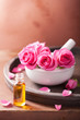 mortar with rose flowers and essential oil for aromatherapy and