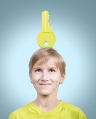 Studio portrait of a boy with a big key