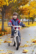 happy boy in autumn park rides his bike