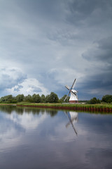 windmill by river over clouded stormy sky