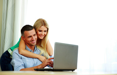 Happy couple using laptop together at home