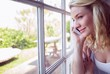 Pretty blonde sitting by the window on a phone call