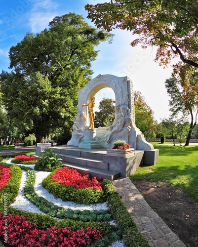 The arch frames the bronze statue of Johann Strauss