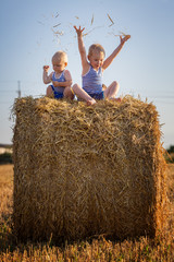 Children play sitting on a haystack