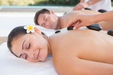 Attractive couple enjoying hot stone massage poolside