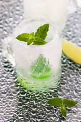 glass made of ice with vodka, lemon and mint