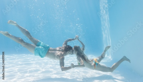 Cute couple holding hands underwater in the swimming pool