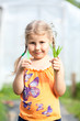 Young girl showing scissors and green plant in hands