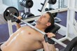 Shirtless bodybuilder lifting heavy barbell weight lying on benc