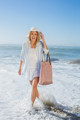 Laughing blonde in sunhat walking in the sea