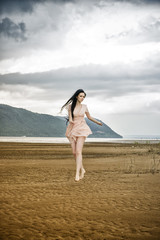 Beautiful young woman runs along the beach