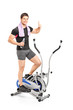 Young guy exercising on a cross trainer machine