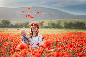 Woman with baby in a field of red poppies