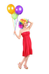 Silly woman with wig holding balloons
