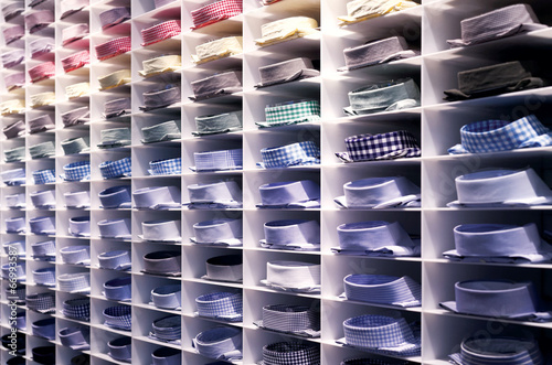 Folded colorful suit shirts on clothes rack