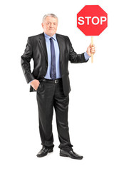 Mature businessman holding a stop sign
