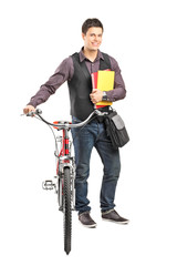 Male student holding books and pushing a bike