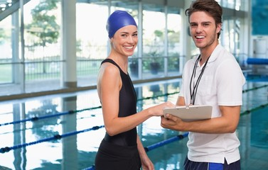 Swimmer smiling at camera with her coach by the pool