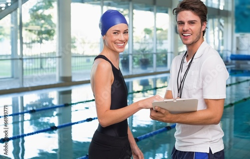 Swimmer smiling at camera with her coach by the pool - 66993771