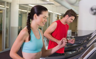 Fit happy couple running together on treadmills