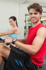 Smiling man working out on the rowing machine