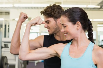 Fit attractive couple comparing biceps