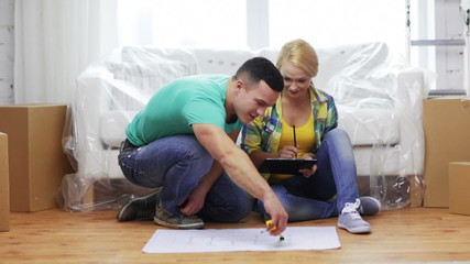 smiling couple looking at blueprint in new home