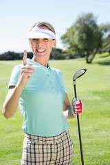 Female golfer standing and pointing up
