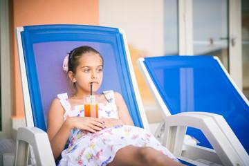 girl on a deckchair drinking juice