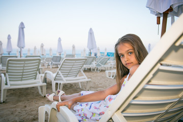girl on a deckchair on the beach in the evening after sunset