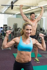 Happy muscular man and woman lifting weights