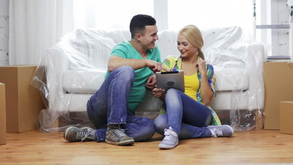 smiling couple with tablet pc in new home