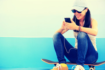 woman skateboarder listening music from smart phone mp3 player