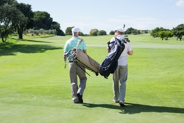 Golfer friends walking holding their golf bags