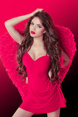 Beautiful girl angel model dancing with wings and long wavy hair