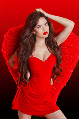 Beautiful brunette fashion girl model posing in red dress with w