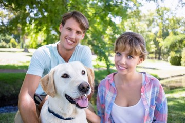 Cute couple with their labrador dog in the park