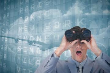 Composite image of suprised businessman looking through binocula