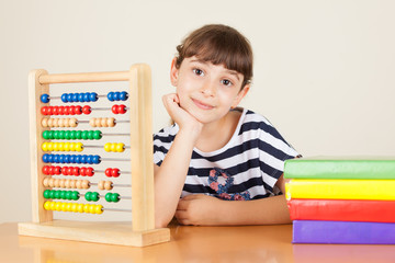 Girl Sitting near Colorful abacus and books