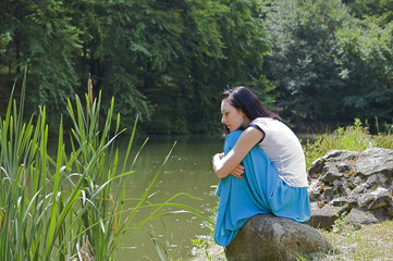 pretty woman wearing blue skirt posing in nature and sitting on