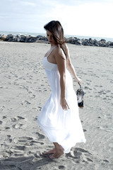 Gorgeous lady on the beach dancing with white dress