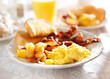 Leinwandbild Motiv full breakfast with scrambled eggs, fried potatoes and bacon,