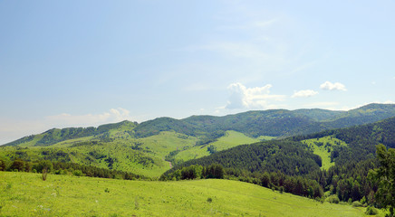 Beautiful summer alpine panorama with green wooded hills