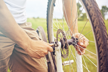 Man checks wheel of bicycle