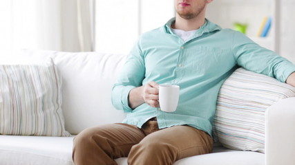 man sitting and drinking from a cup at home