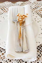 White plate serviette fork knife dried flowers crochet doily