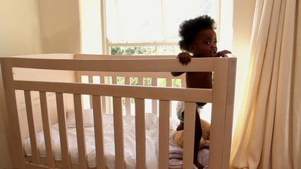 Cute baby girl standing in her crib looking at camera