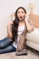 beautiful brunette talking on telephone and sitting floor.