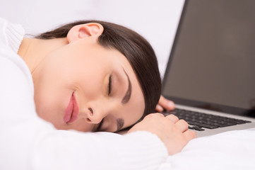 closeup of beautiful brunette sleeping on desk.