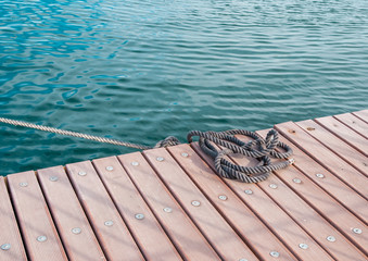 Coiled marine rope on wooden pier